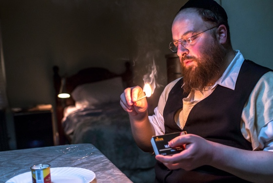 Menashe lights a sad little bachelor candle in a can...