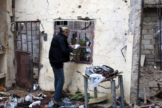 Marie Colvin taking notes at the bombed-out shell of a house in Homs where four old ladies were killed by their president. (Photo by Paul Conroy.)